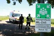 Nahaufnahme des Schildes an einem Rettungstreffpunkt; im Hintergrund zwei Personen und ein Krankenwagen (Foto: Martin Kolbe).