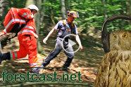 """Sanitäter und Waldarbeiter im Wald. Daneben Portrait einer Eule mit Kopfhörern und der Schriftzug """"forstcast.net"""" (Foto: M. Kolbe)."""