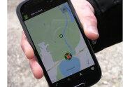 """Nahaufnahme einer Hand mit Smartphone, auf dem die App """"Hilfe im Wald"""" geöffnet ist (Foto: Michael Wolf)."""