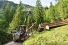 Forwarder stapelt Holz auf Polter am Wegrand